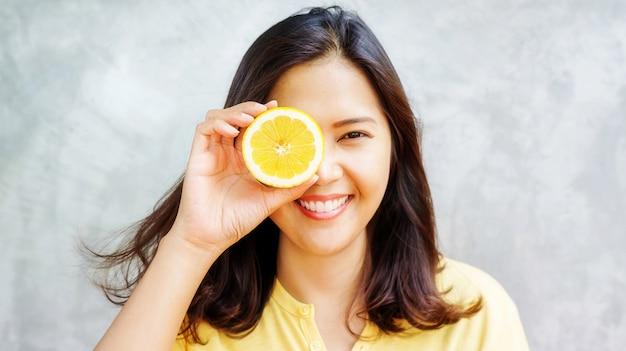 Asiatische frau, die eine gelbe zitrone anhält