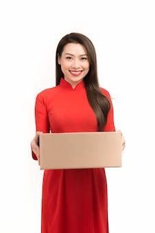 Asiatische frau, die eine geschenkbox in einer geste des gebens im frühlingsfest hält
