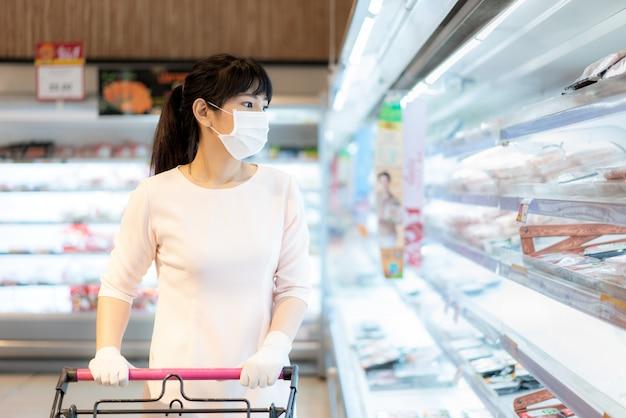 Asiatische frau, die eine gesichtsmaske in einem supermarkt trägt