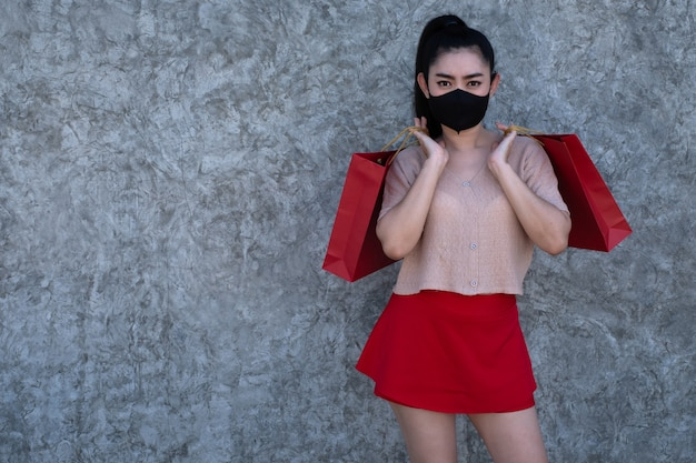 Asiatische frau, die eine gesichtsmaske trägt und einkaufstüten am betonwandhintergrund hält