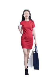 Asiatische frau, die eine kaffeetasse hält und einkaufstaschen lokalisiert über weißem hintergrund trägt