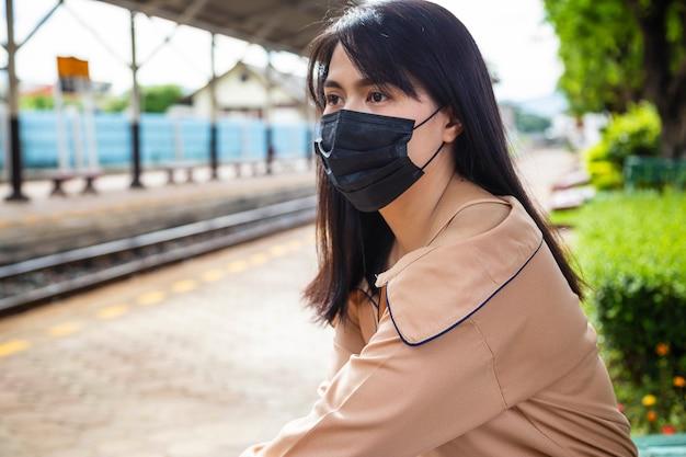 Asiatische frau, die eine maske trägt, um covid-19 oder covid-19-konzept zu verhindern