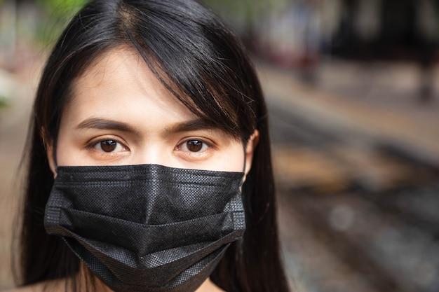 Asiatische frau, die eine maske trägt, um covid-19 zu verhindern