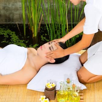 Asiatische frau, die eine massage in der tropischen einstellung hat