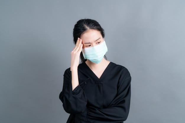 Asiatische frau, die eine medizinische gesichtsmaske trägt, schützt filterstaub pm2.5 gegen umweltverschmutzung, anti-smog und covid-19 und hat kopfschmerzen auf grauem hintergrund