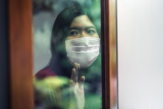 Asiatische frau, die eine medizinische maske trägt, bleibt zu hause isoliert, um sich beim ausbruch von covid19 unter quarantäne zu stellen