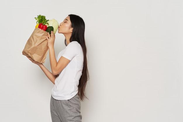 Asiatische frau, die eine papiertüte mit obst und gemüse hält