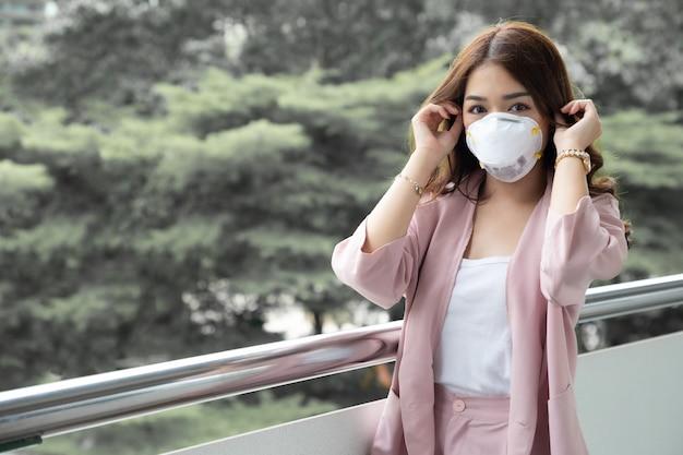 Asiatische frau, die eine schützende gesichtsmaske für das pest-coronavirus trägt. hygienemaske für die sicherheit im freien umweltbewusstsein oder virusverbreitungskonzept