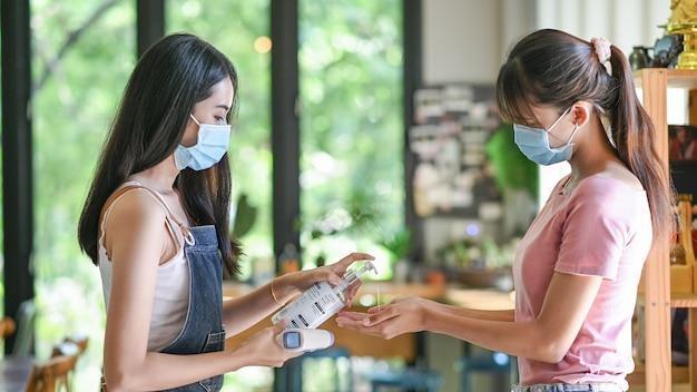 Asiatische frau, die eine schutzmaske mit antiseptischem alkoholgel trägt, verhindert den ausbruch von covid-19 im café