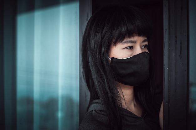 Asiatische frau, die eine schwarze gesichtsmaske trägt, geistesabwesend an der tür steht und zu hause für selbstquarantäne und soziale distanzierung im coronavirus- oder covid-2019-ausbruchssituationskonzept bleibt