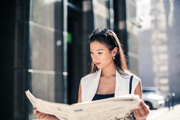 Asiatische frau, die eine zeitung liest