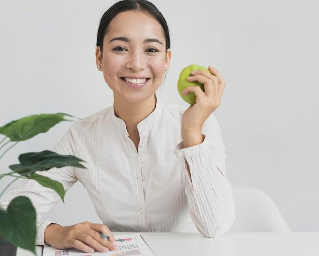 Asiatische frau, die einen apfel anhält