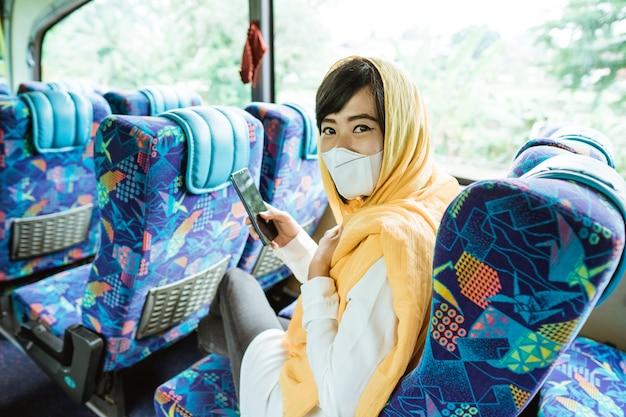 Asiatische frau, die einen öffentlichen transport trägt, der gesichtsmaske während pandemie trägt