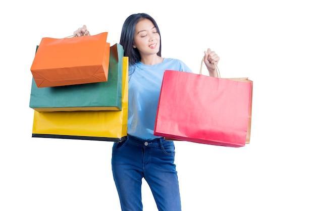 Asiatische frau, die einkaufstaschen lokalisiert über weißem hintergrund trägt