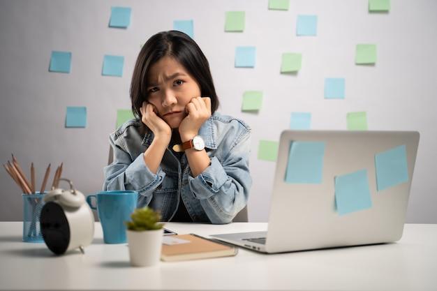 Asiatische frau, die ernsthaft an einem laptop zu hause arbeitet. . von zuhause aus arbeiten. prävention coronavirus covid-19-konzept.