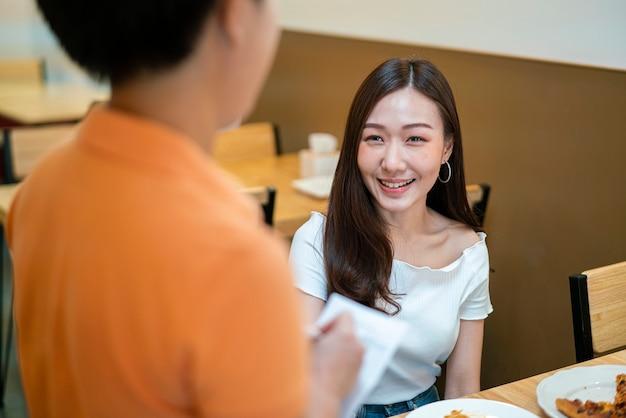 Asiatische frau, die essen zur kellnerin für ihr abendessen im restaurant bestellt.