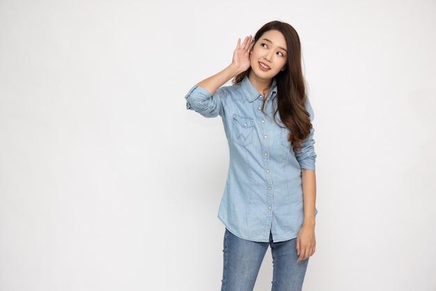 Asiatische frau, die etwas hört, indem sie die hand auf das ohr legt, isoliert auf weißem hintergrund