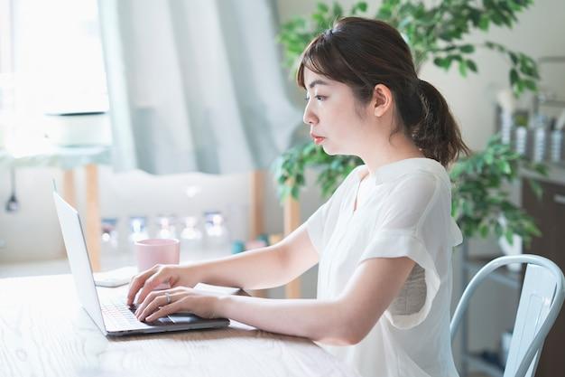 Asiatische frau, die fernarbeit mit laptop tut