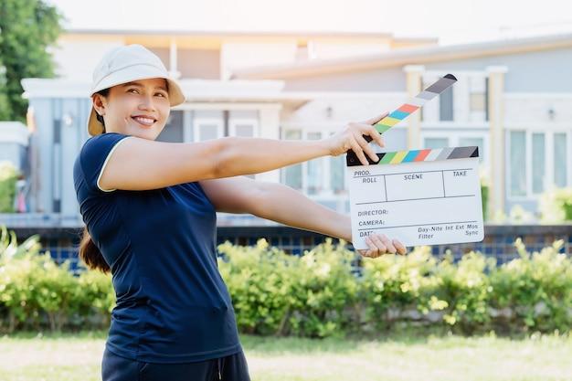 Asiatische frau, die filmschieferfarbentafel für filmkino und fernsehindustrie hält