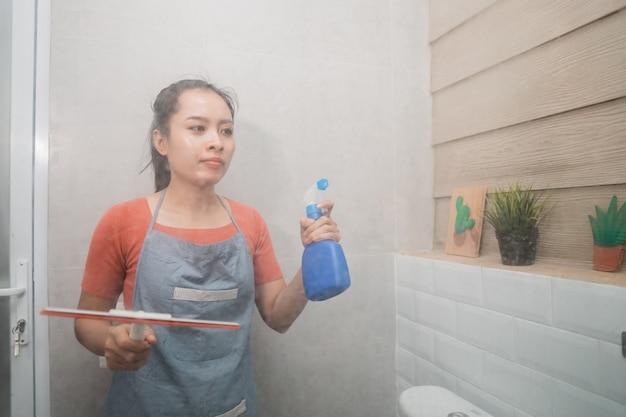 Asiatische frau, die flaschenspray und scheibenwischer hält, während das toilettenglas im badezimmer reinigt