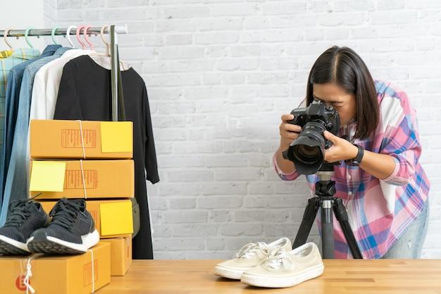 Asiatische frau, die foto zu schuhen mit digitalkamera für post zum online-verkauf im internet nimmt