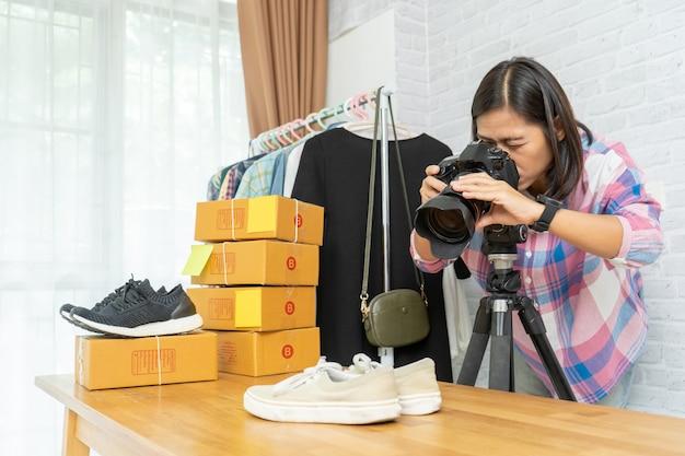 Asiatische frau, die foto zu schuhen mit digitalkamera für post zum online-verkauf nimmt
