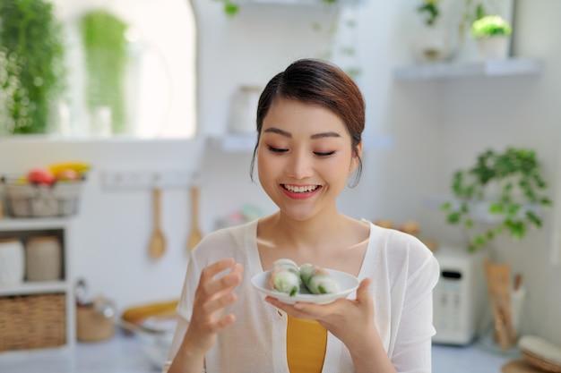 Asiatische frau, die frühlingsrollen auf küchenhintergrund isst