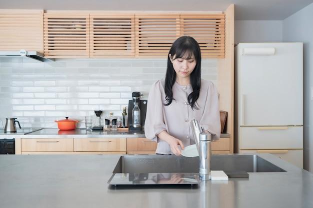 Asiatische frau, die geschirr in der küche des hauses spült