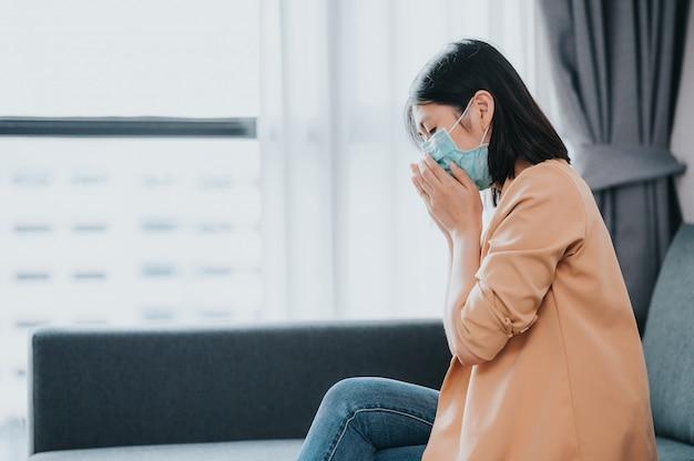 Asiatische frau, die gesichtsmaske hustet und sich im wohnzimmer krank fühlt