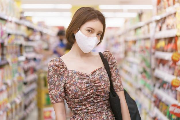 Asiatische frau, die gesichtsmaske im suppermarkt während der epidemie covid-19 trägt.