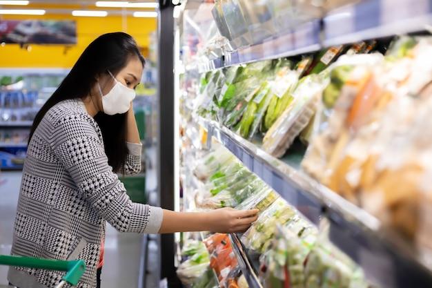 Asiatische frau, die gesichtsmaske trägt auswahlgeschäft gemüse mit einkaufswagen im suppermarket-kaufhaus.