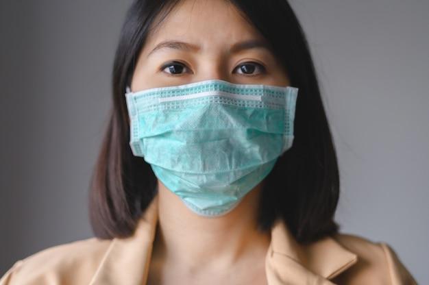 Asiatische frau, die gesichtsmaske trägt