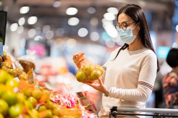 Asiatische frau, die gesichtsmaskeneinkauf im supermarkt während des koronavirus trägt