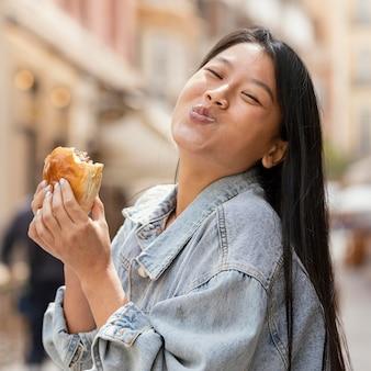 Asiatische frau, die glücklich ist, nachdem sie straßenlebensmittel gekauft hat