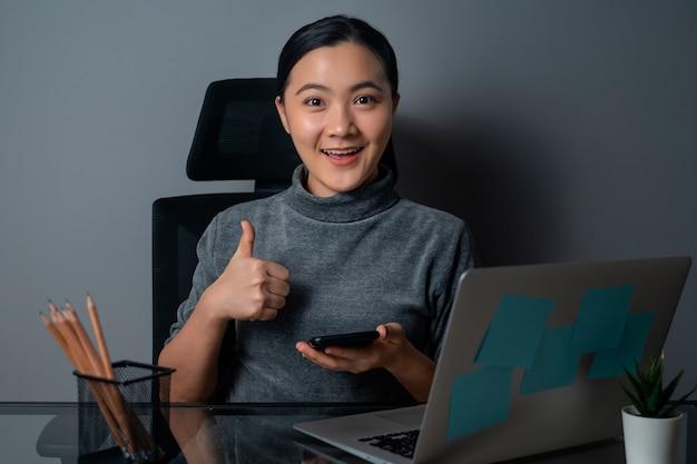 Asiatische frau, die glücklich zeigt daumen oben, kamera betrachtend, an einem laptop im büro arbeitend