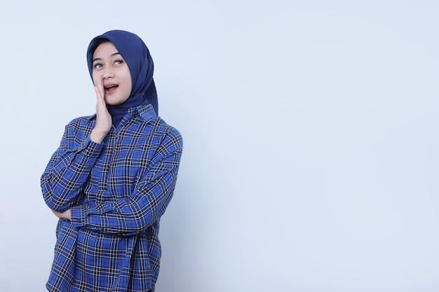 Asiatische frau, die glückliches und glückliches tragen von hijab unterstützt, während sie auf weißer wand flüstert