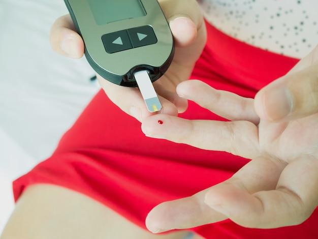 Asiatische frau, die glukosespiegel mit digitalem glukosemessgerät misst, diabetes-test