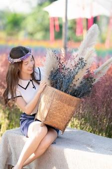 Asiatische frau, die grasblumenkorb am morgen am blumenfeld aufwirft und hält.