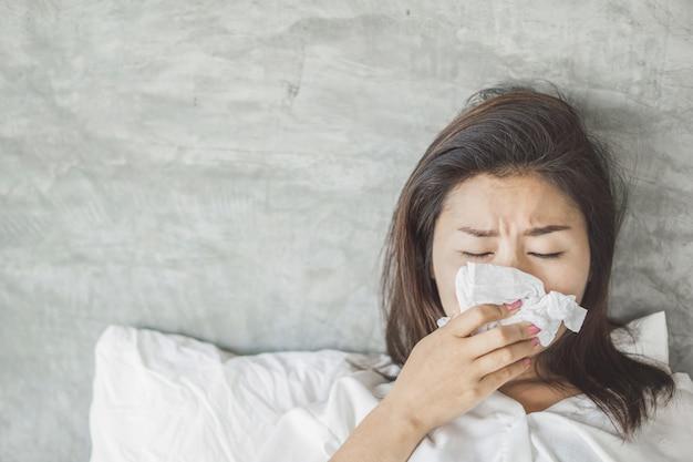 Asiatische frau, die grippe hat und auf bett niest