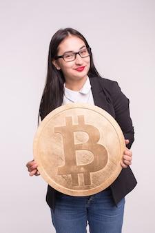 Asiatische frau, die großes bitcoin auf weiß hält. kryptowährungs-investitionskonzept.