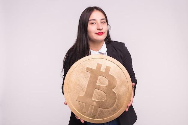 Asiatische frau, die großes bitcoin auf weiß hält.