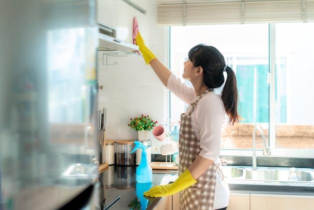 Asiatische frau, die gummihandschuhe trägt, die küchenschränke in ihrem haus während des aufenthalts zu hause mit freizeit über ihre tägliche haushaltsroutine reinigen.