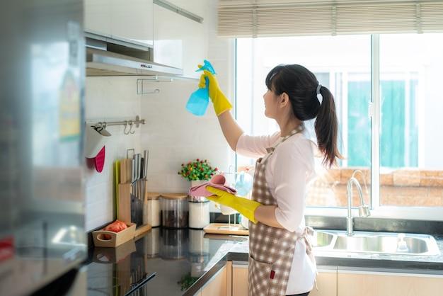 Asiatische frau, die gummischutzhandschuhe trägt, die küchenschränke in ihrem haus reinigen