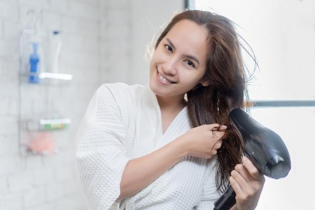 Asiatische frau, die haartrockner nach dusche im badezimmer verwendet