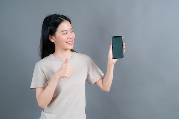 Asiatische frau, die handy-anwendungen verwendet, genießt die fernkommunikation online in sozialen netzwerken oder das einkaufen isoliert