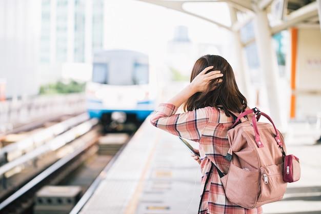 Asiatische frau, die himmelzug wartet und chirurgische gesichtsmaske gegen neuartiges coronavirus oder coronavirus-krankheit am öffentlichen bahnhof trägt