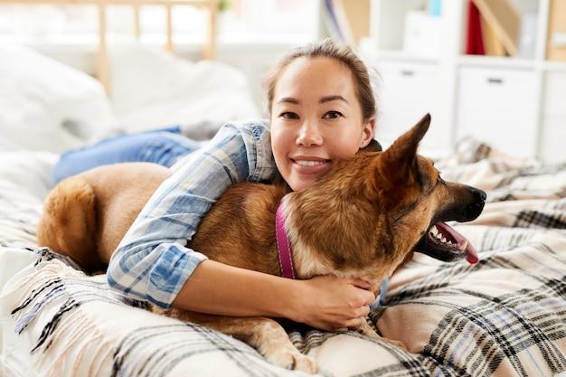 Asiatische frau, die hund umarmt