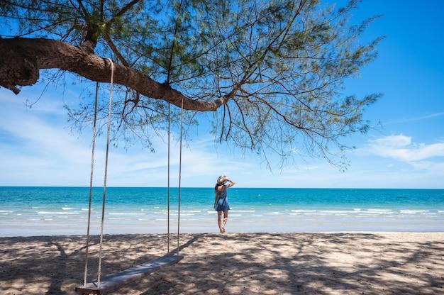 Asiatische frau, die hut trägt, der auf dem strand und hölzerne schaukel geht, die vom baum im tropischen meer hängen