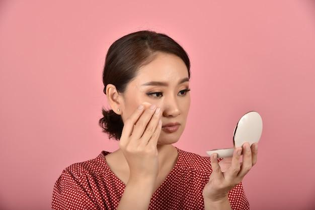 Asiatische frau, die ihr gesichtsproblem im spiegel betrachtet, weibliches gefühl, das über ihr reflexionsaussehen ärgerlich ist, zeigen die zeichen der alternden haut, make-up-abdeckungs-hautproblem.