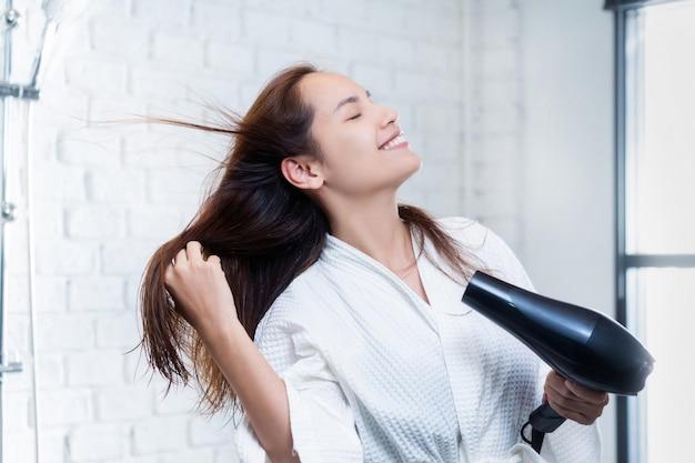 Asiatische frau, die ihr haar nach dem duschen trocknet